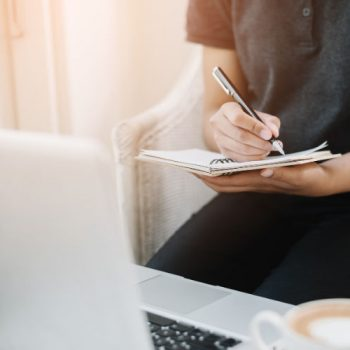 Woman writing in notepad in front of laptop