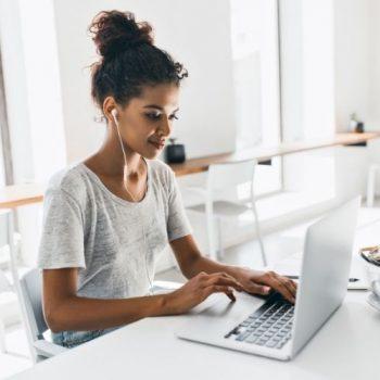 young woman at laptop writing a blog post